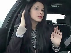 Raven haired babe lights up a cigarette in the car