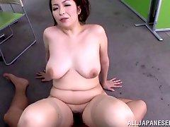 Charming matured Japanese dame with big tits giving her guy titjob