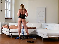 Strict mistress in latex corset spanks sexy chick on a leash